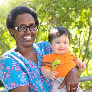 Nurse smiling with and holding young boy outside
