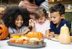 Three young kids carving a pumpkin