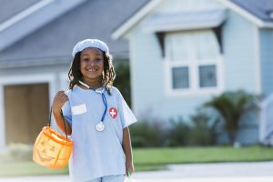 Little boy dressed up as a surgeon with a pumpkin basket, out trick-or-treating