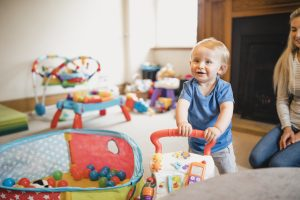 A young boy playing with a push toy
