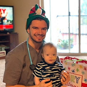 Nurse Vadim wearing an elf hat and holding patient Saylor