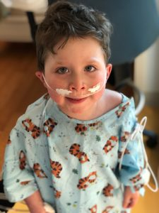 Lukas in a hospital with oxygen, smiling at the camera