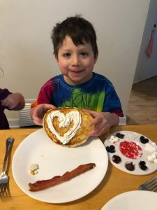 Lukas sitting at the table, smiling and holding a pancake with a whipped cream heart