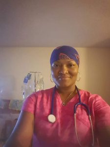 Nurse Tia in patient's home wearing scrubs and a stethoscope, smiling at the camera